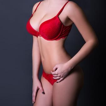 Primo piano del corpo femminile sexy in lingerie di pizzo rosso su sfondo grigio scuro