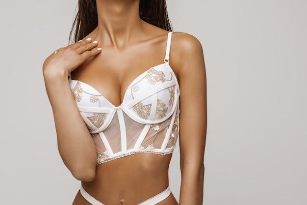 Chiuda sull'ente femminile sexy nella posa bianca del reggiseno isolato