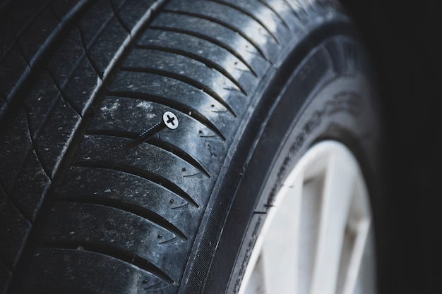 Chiuda in su della vite di metallo tagliente che perfora in un pneumatico di automobile