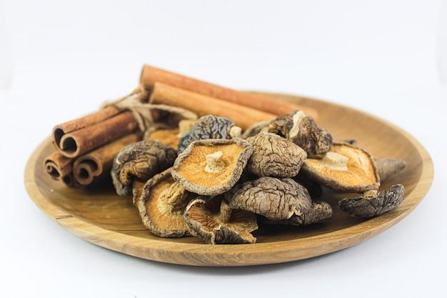 Close up funghi shitake e cannella nel piatto di legno