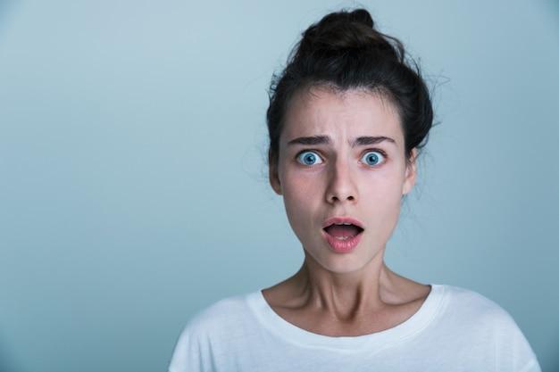 Primo piano di una giovane donna scioccata che indossa la maglietta isolato su sfondo blu