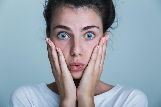 Primo piano di una giovane donna scioccata che indossa la camicia del serbatoio isolato su sfondo blu