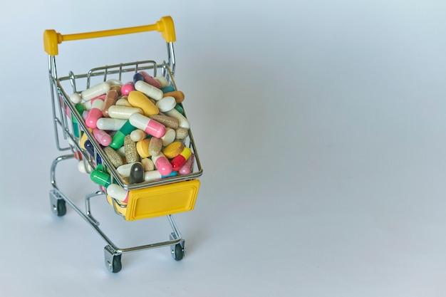 Il primo piano di un carrello della spesa ha riempito di pillole variopinte. carrello dal supermercato con diverse medicine.