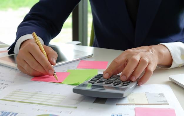 Il colpo del primo piano degli analisti usa un calcolatore e una penna per valutare la situazione fluttuante del mercato azionario.