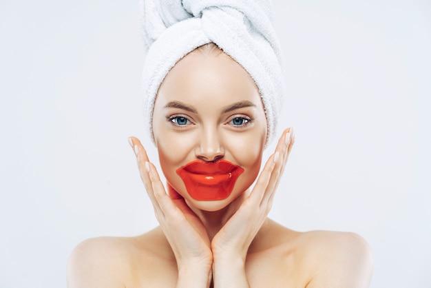 Immagine ravvicinata di giovane donna attraente tocca delicatamente le guance, applica cerotti di collagene per labbra secche, gode di routine di bellezza a casa dopo aver fatto la doccia, usa cosmetici coreani, posa nuda al coperto