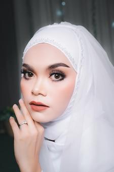 Colpo del primo piano di una bella sposa musulmana asiatica con trucco in abito da sposa bianco e hijab