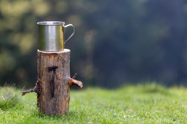Colpo del primo piano, grande tazza brillante della latta sul ceppo di albero isolato all'aperto sulla foresta erbosa di estate soleggiata