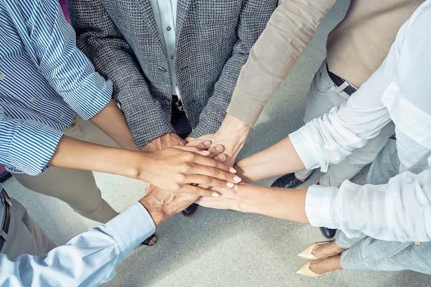 Immagine ravvicinata di uomini d'affari che uniscono le mani e sorridono celebrando il successo mentre