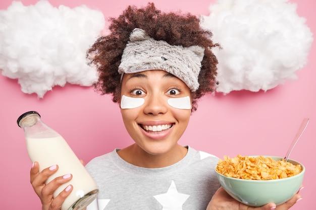 Immagine ravvicinata di allegra ragazza afroamericana sorride ampiamente gode di nuovo giorno andando a fare colazione pone con cereali e latte indossa indumenti da notte benda sulla fronte pone al coperto