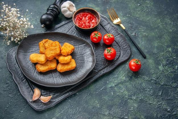 Immagine ravvicinata di pepite di pollo su un piatto nero e un'elegante forchetta ketchup su vassoio di colore scuro fiori bianchi pomodori con gambo