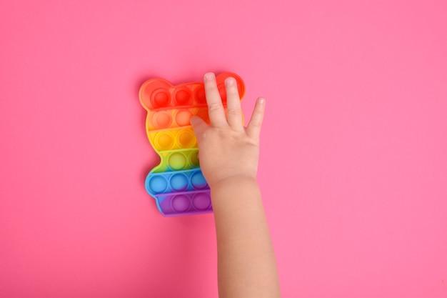 Un primo piano delle mani dei bambini che giocano con il popolare giocattolo pop it fidget. un bambino con un giocattolo tattile colorato e flessibile lo fa scoppiare.