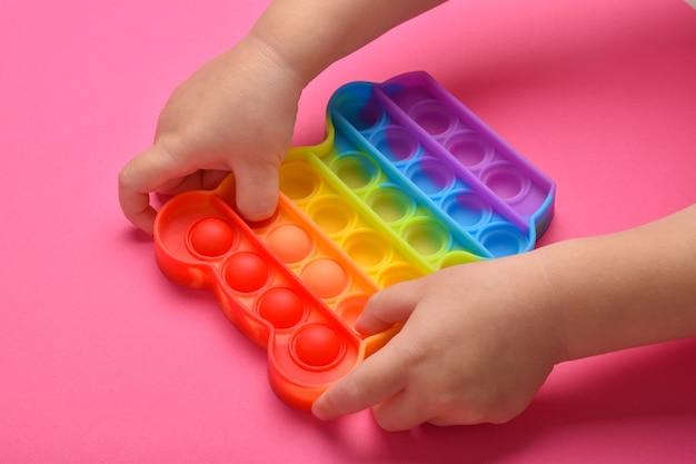 Un primo piano delle mani dei bambini che giocano con il popolare giocattolo pop it fidget.