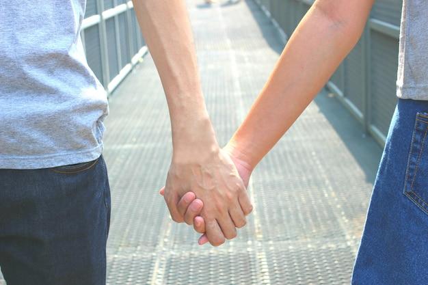 Vicino colpo di mano coppia tenendo insieme il concetto di amore, cura, incoraggiamento e relazione