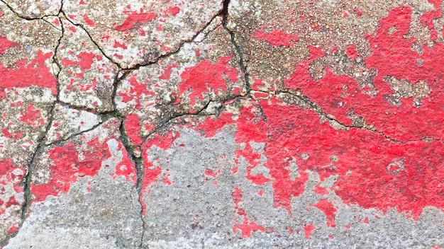 Immagine ravvicinata del vecchio fondo di struttura della superficie della parete rossa incrinata