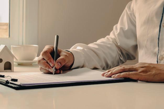 Primo piano del cliente che firma un contratto immobiliare con modulo di richiesta mutuo approvato, mutuo per la casa e idee per il prestito di assicurazione sulla casa.