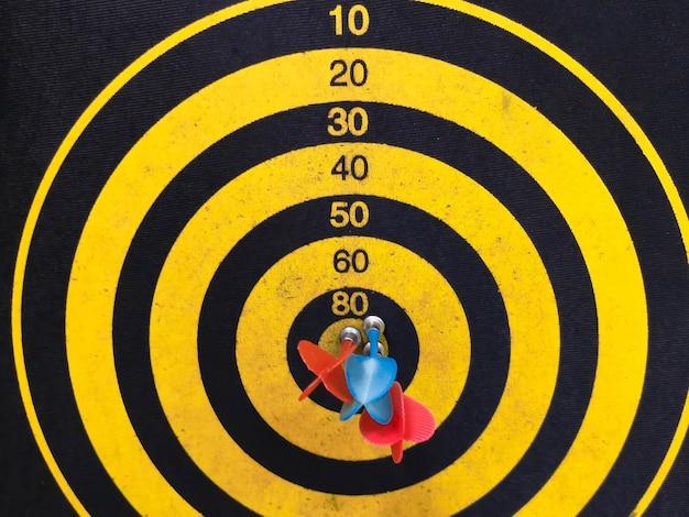 Primo colpo di un bersaglio per le freccette. freccia di freccette manca il bersaglio su un bersaglio per le freccette durante il gioco. freccette gialle.