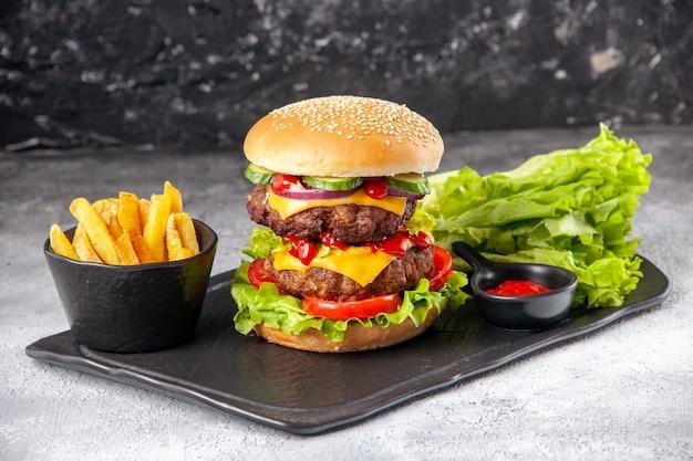 Immagine ravvicinata di deliziosi panini fatti in casa e patatine fritte ketchup verde su vassoio nero su superficie isolata grigia in difficoltà