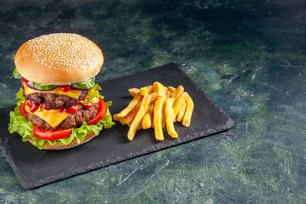 Immagine ravvicinata di deliziosi sandwich e patatine fritte sul vassoio di colore scuro sul lato destro su superficie nera