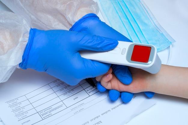 Primo piano delle mani del medico in guanti medici pronti per l'uso del termometro a infrarossi per controllare la temperatura corporea per i sintomi del virus - concetto di epidemia di virus epidemico covid-19.
