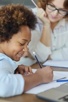 Immagine ravvicinata di una studentessa adolescente di razza mista entusiasta che scrive con la matita durante una lezione con