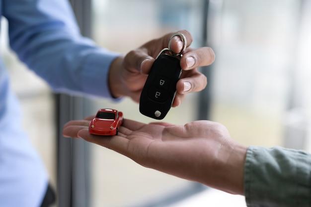 Primo piano dello scambio di chiavi dell'auto e modellini di auto, concetto finanziario, assicurazione, sequestro di auto.