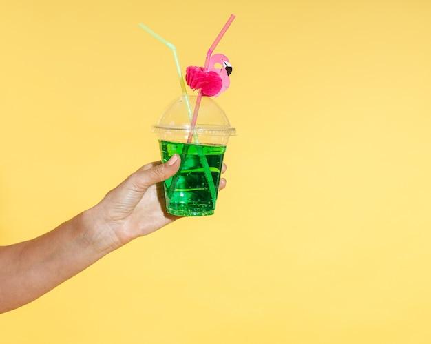 Immagine ravvicinata di una mano femminile che tiene un cocktail tropicale rinfrescante con cannuccia di fenicottero