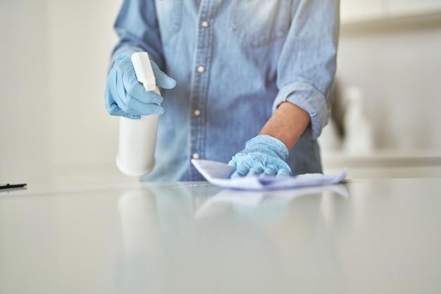 Immagine ravvicinata di mani femminili in guanti di gomma usando spray detergente e panno durante la pulizia
