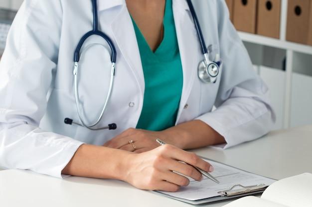 Colpo del primo piano delle mani del medico femminile che riempiono il modulo di registrazione paient. posto di lavoro del dottore. sanità e concetto medico.