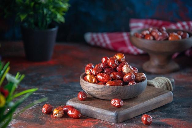 Immagine ravvicinata di frutti freschi di silverberry crudi in una ciotola su un tagliere di legno su sfondo di colori misti