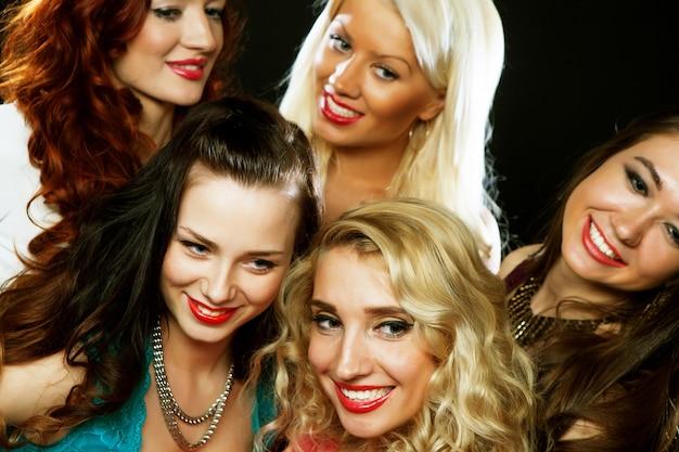 Primo piano di un gruppo di ragazze ridenti che fanno festa, scatta selfie con lo smartphone
