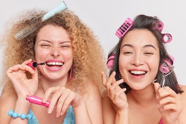 Chiuda sul colpo di felice razza mista amiche divertirsi fare trucco applicare mascara tenere ciglia bigodino fare acconciatura con rulli prepararsi per la data esprimere emozioni positive posa insieme al coperto