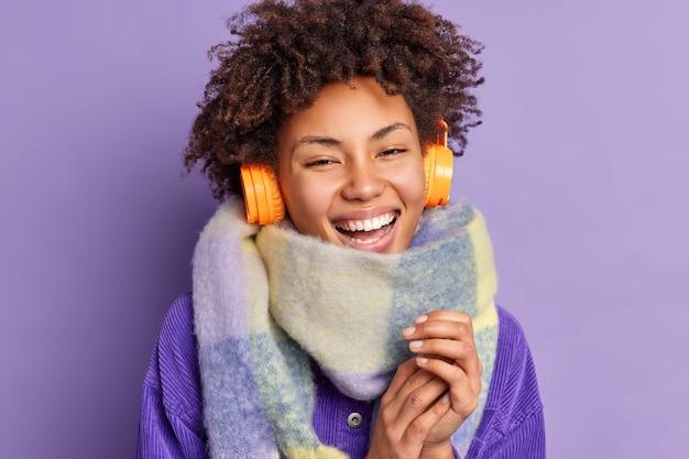 Immagine ravvicinata di felice giovane donna afroamericana tiene le mani unite sorride indossa ampiamente sciarpa intorno al collo utilizza cuffie wireless per ascoltare musica gode di un buon suono