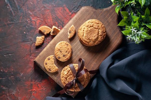Immagine ravvicinata di deliziosi biscotti di zucchero fatti in casa su tavola di legno e vaso di fiori su sfondo scuro di colori misti