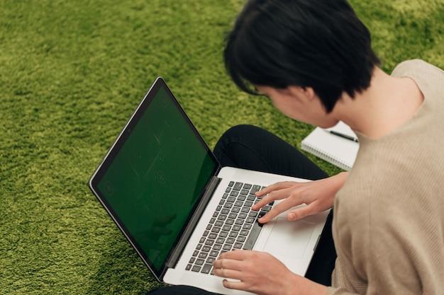 Colpo del primo piano delle mani umane poste sopra il computer portatile.