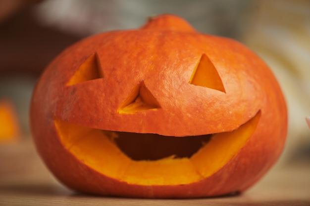 Close-up shot jack-o'-lantern scolpito nella zucca matura arancione per la festa di halloween a casa