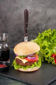 Immagine ravvicinata di coltello in delizioso panino di carne e pepe verde su vassoio nero salsa ketchup pomodori con gambo su superficie grigia