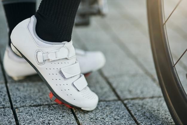 Immagine ravvicinata delle gambe di una ciclista che indossa scarpe da ciclismo in piedi con la sua bici