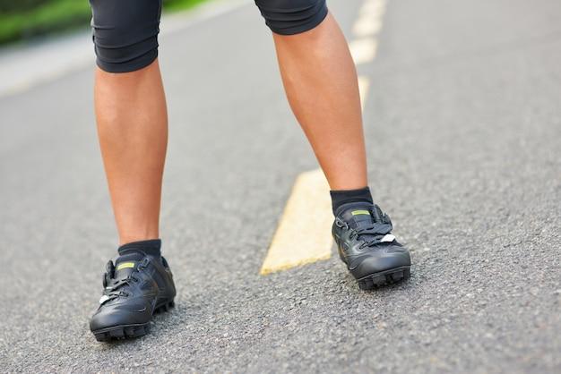 Immagine ravvicinata delle gambe di un ciclista professionista che indossa scarpe da ciclismo in piedi sul