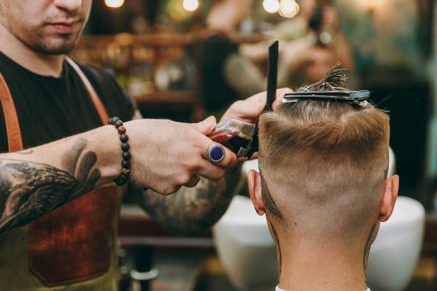 Immagine ravvicinata dell'uomo che ottiene taglio di capelli alla moda al negozio di barbiere. l'hairstylist maschile in tatuaggi al servizio del cliente.