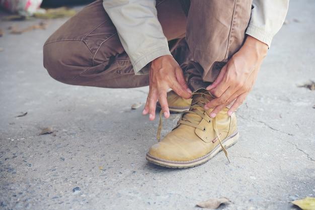 Immagine ravvicinata delle mani dell'uomo legate con i lacci per i suoi stivali marroni da costruzione