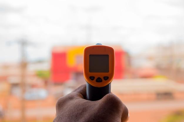 Primo piano di un uomo pronto per l'uso del termometro frontale a infrarossi (pistola termometro) per controllare la temperatura corporea per i sintomi del virus - concetto di epidemia di virus epidemico