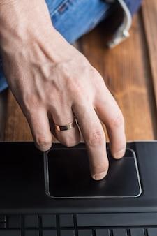 Colpo del primo piano del trackpad commovente della mano degli uomini sul computer portatile. spazio vuoto sui tasti. fondale in legno