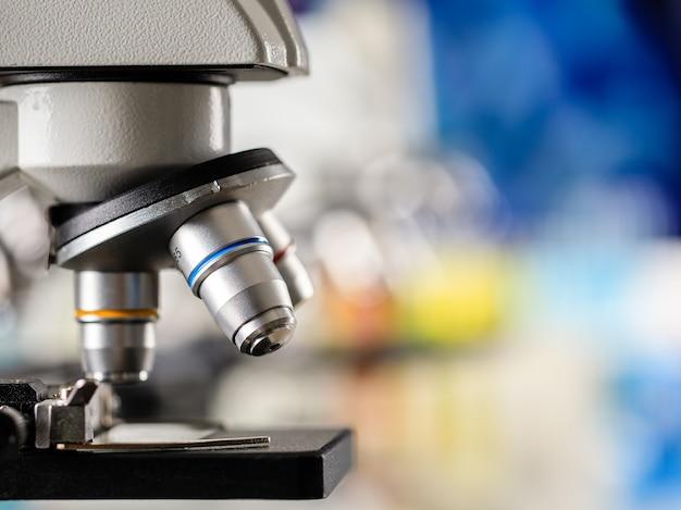 Immagine ravvicinata della lente del microscopio e della copia dello sfondo sfocato colorato.
