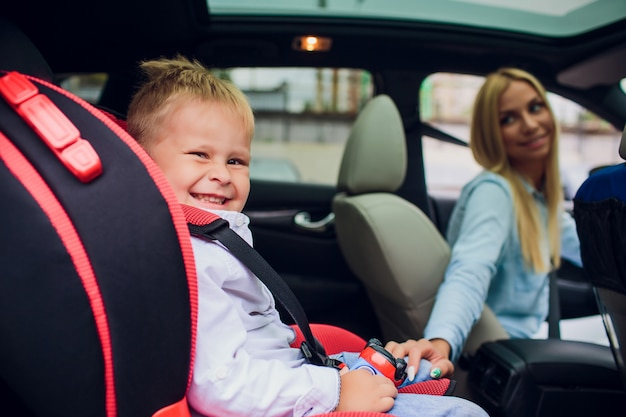 Close-up shot madre guida auto, cintura di sicurezza con fibbia. figlio sul sedile posteriore. famiglia alzando i pollici