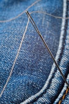 Colpo del primo piano dell'ago con filo sul materiale dei jeans. avvicinamento.