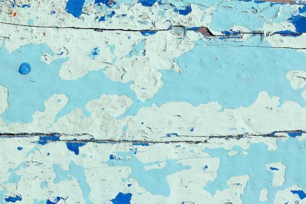 Immagine ravvicinata della vecchia struttura di vernice blu chiaro che si staccava dallo sfondo della tavola di legno