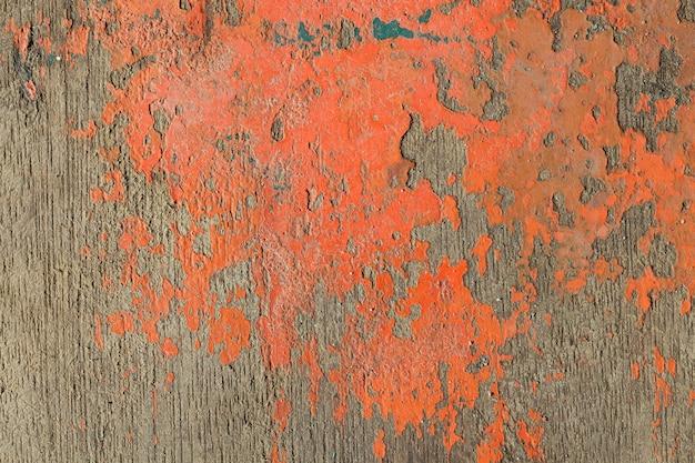 Immagine ravvicinata della vecchia trama di vernice arancione che si staccava dallo sfondo della tavola di legno