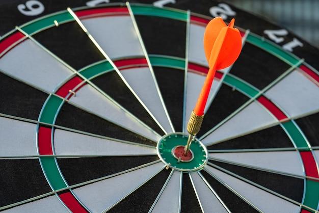 Chiuda sulla freccia rossa del dardo del colpo che colpisce nel centro dell'obiettivo del bersaglio, dell'obiettivo aziendale o del concetto di successo dell'obiettivo.