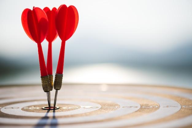 Chiuda sulle frecce rosse dei dardi del colpo nel centro dell'obiettivo. concetto di successo dell'obiettivo di affari.