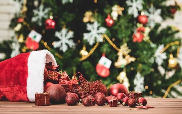 Immagine ravvicinata di elementi decorativi rossi stella sfera presente scatole regalo versando dal cappello di natale sul tavolo di legno davanti a un bellissimo arredamento completamente con fiocchi di ghiaccio calzini albero di pino in sfondo sfocato.